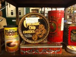 Koekjesdozen met stickers 'Gespen ceinturen te vermaken' met daarnaast een koffiedoos van De Roode Pelikaan